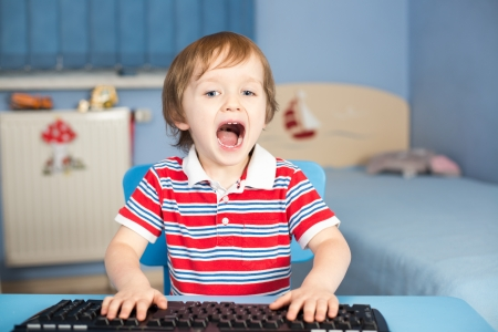 Little baby boy screaming when typing on keyboard in his room photo