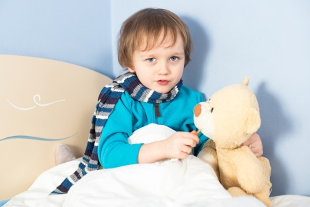 body temperature: Little sick baby boy checking teddy bears body temperature in bed