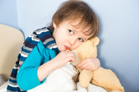 Sick little boy checking his body temperature and holding teddy bear photo