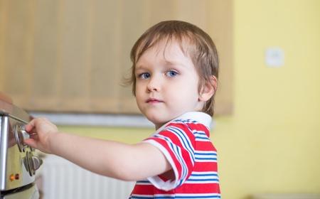Little baby boy berührt Herd - Gefahr in der Küche