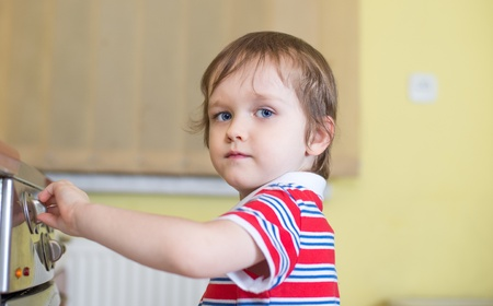 Little baby boy is touching cooker - danger in kitchen