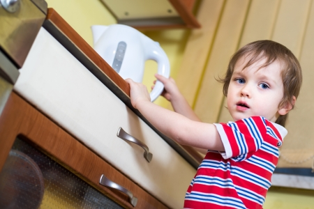 eletrical: Little baby boy is reaching eletrical kettle with hot water - danger in kitchen Stock Photo
