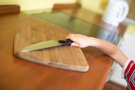 Little baby boy is reaching kitchen knife - danger in kitchen Stock Photo - 17106830