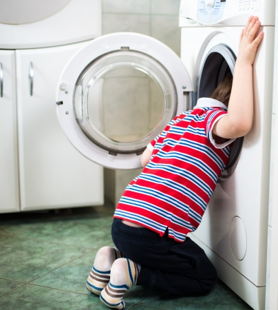 Little baby boy dangerously putting his head into washing machine - danger in bathroom Stock Photo