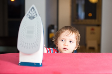 Little baby boy is reaching to hot iron - danger at home