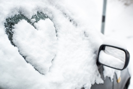 Buried by snow car with painted heart on side window