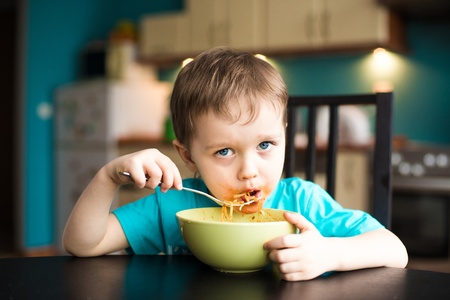 slurp: Little boy is eating spaghetti with souce on his face Stock Photo