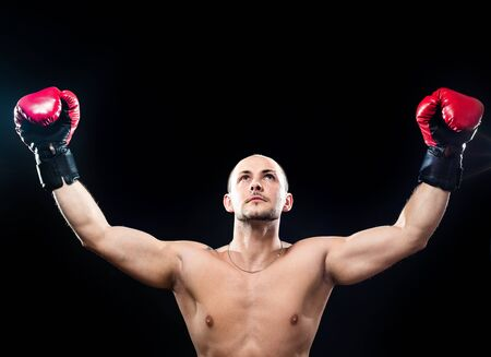 Muscular boxer in victory gesture isolated on black photo