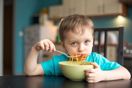 ni�os comiendo: 3 a�os viejo, mientras que comer espaguetis Foto de archivo