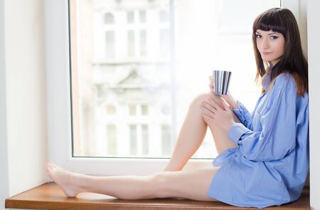 Beautiful brunette in a blue shirt sitting on the windowsill, and drinking coffee or tea photo