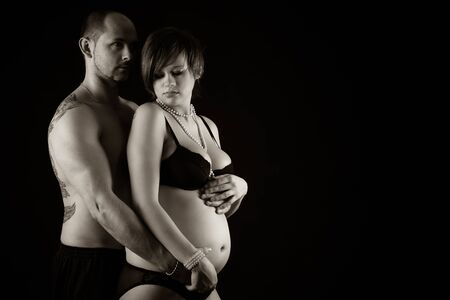Romantic couple in studio  - beautiful pregnant woman with her husband photo