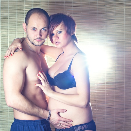 Young pregnant couple in front of bamboo mat photo