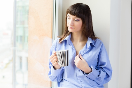 Portrait of young woman in blue shirt drinking coffee and looking out of the window