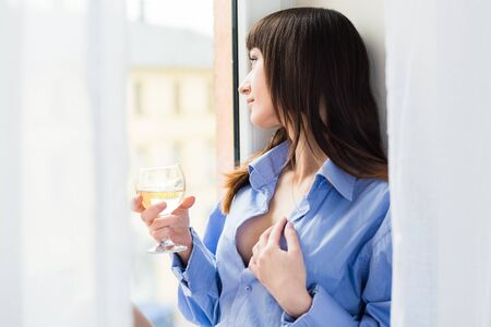 Sexy woman in blue shirt looking through the window and holding a glass of wine photo