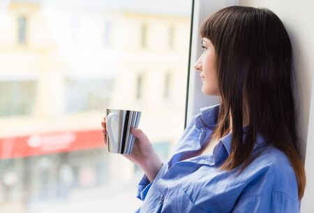 Woman in blue shirt with a cup of tea looking through the window photo