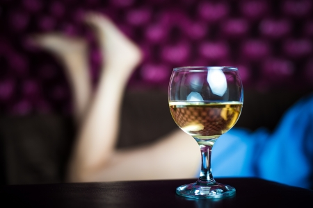 A glass of white wine - sexy womens legs in the background