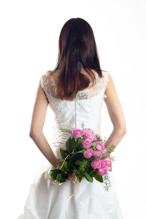 Bride is standing in wedding dress on white background holding roses, view from behind Stock Photo - 18824516