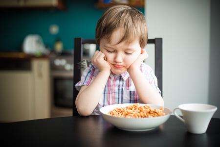 cara triste: Ofendido ni�o peque�o durante espaguetis comer en la cena