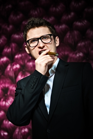 Elegant man wearing glasses and suit - smoking cigar photo