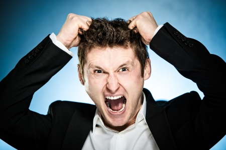Angry businessman pulls his hair out and shouting photo