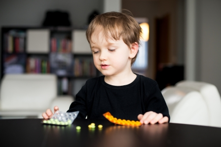 Little boy playing with dangerous medicines