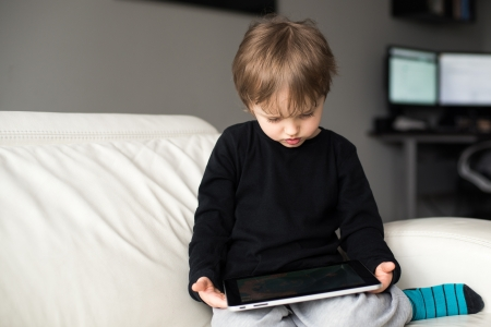 Little boy watching a movie on tablet, indoor photo