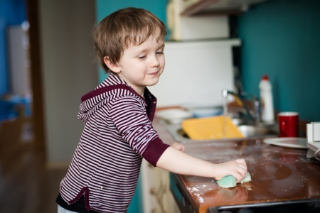 domestic chore: Boy cleaning the kitchen after making dinner