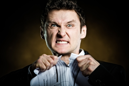 Angry businessman tearing invoice in pieces Stock Photo