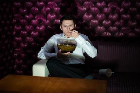 Man watching fascinating program in TV and eating popcorn photo