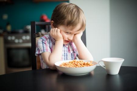 refusing: Offended little boy refuses to eat dinner - spaghetti