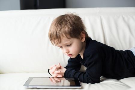 kleiner Junge auf dem Bauch liegend und beobachten eine Geschichte über Touchscreen-Tablet