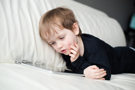 Little three year old boy uses a tablet on a sofa photo