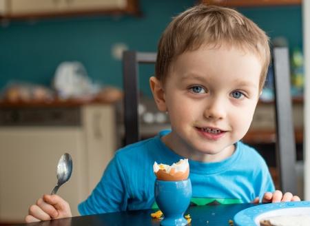 작은 세 살 소년은 아침에 계란을 먹는 스톡 콘텐츠