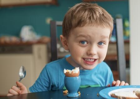 Kleine glücklich Dreijähriger Junge isst ein Ei zum Frühstück