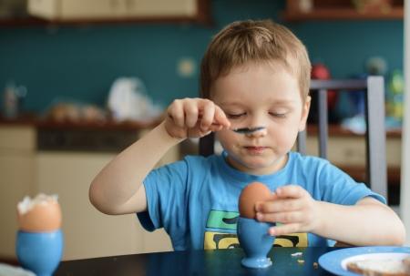 Kleine glücklich drei Jahre alten Jungen bricht das Ei auf Frühstück