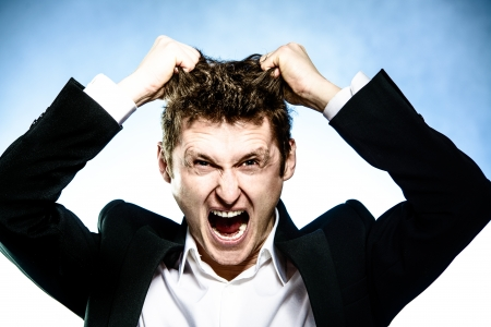 frustrated businessman pulls his hair and screams Banco de Imagens