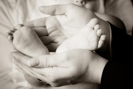 부드럽게 그녀의 신생아 아기의 발을 들고 어머니
