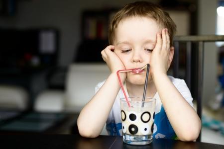 어린 소년 마시는 빨 대를 사용하여 우유의 coctail 음료