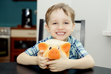 4 year old: 4 year old boy smiling and holding a piggy bank