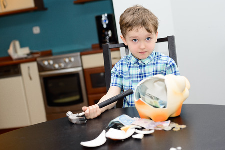 4 year old: 4 year old boy and smashed his piggybank at home Stock Photo