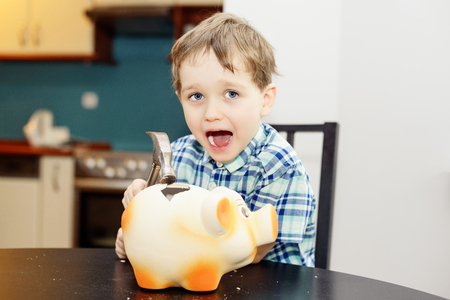 4 year old boy smashed pig piggy bank with a hammer photo