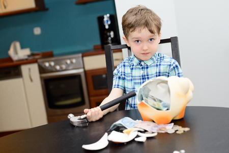 4 year old boy and smashed his piggybank at home Stock Photo