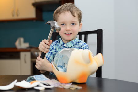 4 year old boy satisfied with breaking the piggy bank at home photo