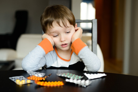 4 year old: worried 4 year old boy sitting at the table with medications at home