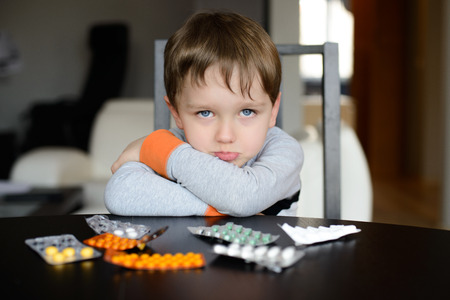 sad preschooler sitting at the table with pills at home