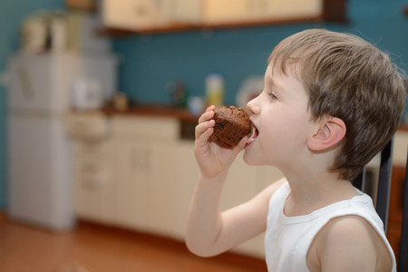 4 year old boy eats chocolate muffin at kitchen photo