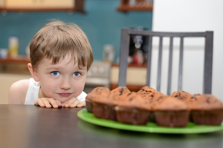 4 year old: 4 year old boy hungrily looking at chocolate cake muffin