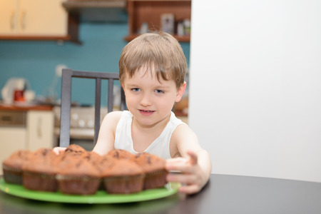 4 year old: 4 year old boy reaching for a chocolate cake at home Stock Photo