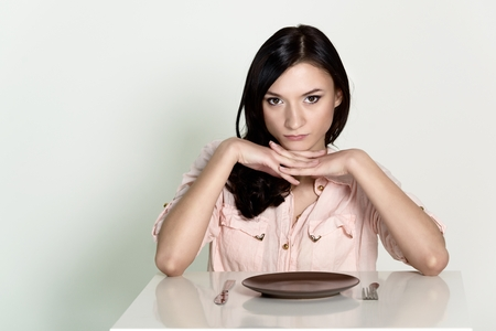 Beautiful brunette woman sitting with an empty plate and wait her lunch. Stock Photo