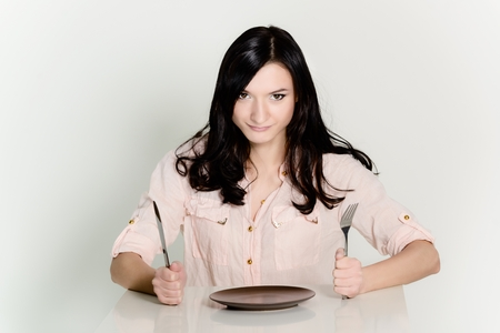 beautiful brunette waiting for food at a restaurant. empty plate in front of her, holding in her hand fork and knife photo